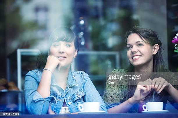 Two Young Women Sitting in Cafe, Smiling, View Through Glass