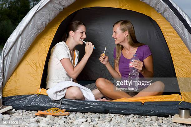 two young women sitting in tent brushing their teeth