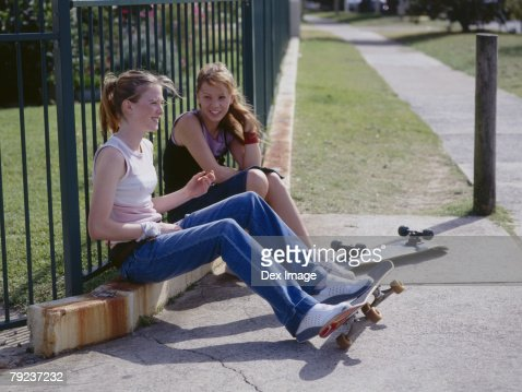 Two young women sitting on curb, chatting : Stock Photo