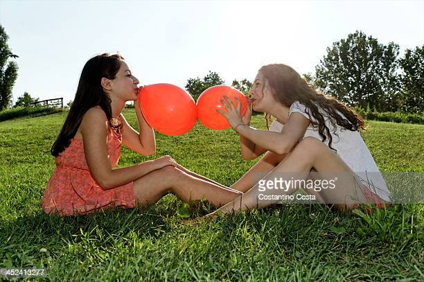 Two young women sitting on grass bowing up red balloons
