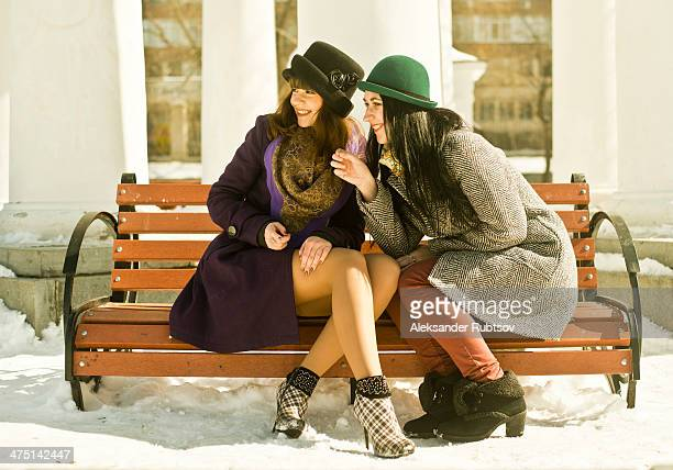 Two young women sitting on park bench in snow