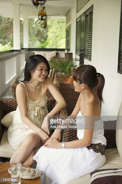 Two young women sitting on patio, talking