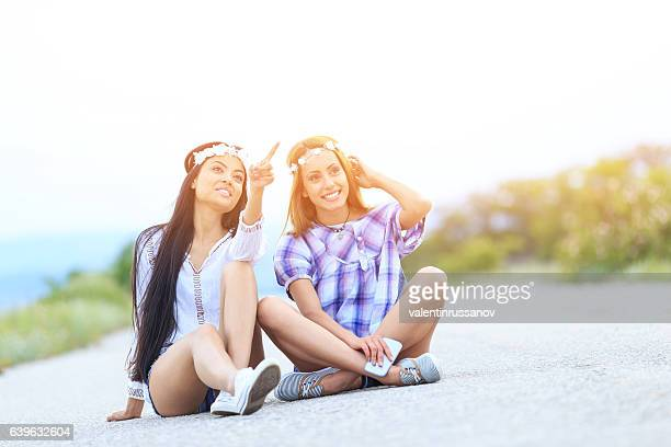 Two young women sitting on road and resting