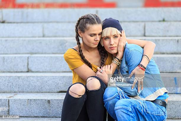 Two young women sitting on stairs and embracing