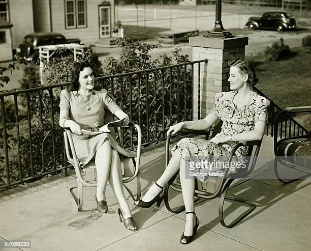 Dos mujeres jóvenes sala de estar en la terraza, hablando, (B & P