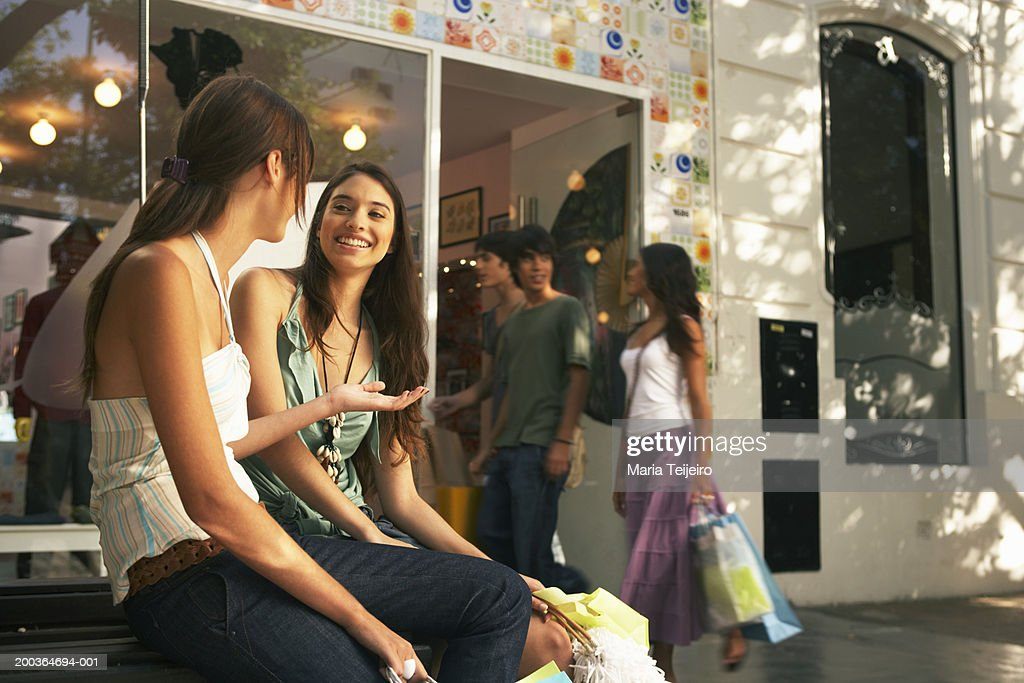 Two young women sitting outdoors by shop, smiling : Stock Photo