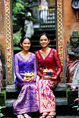 Two young women sitting with offerings, Bali, Indonesia
