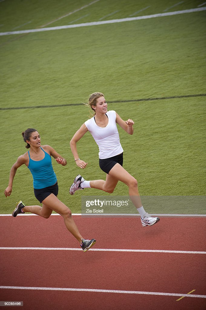 two young women sprinting on track : Stock Photo