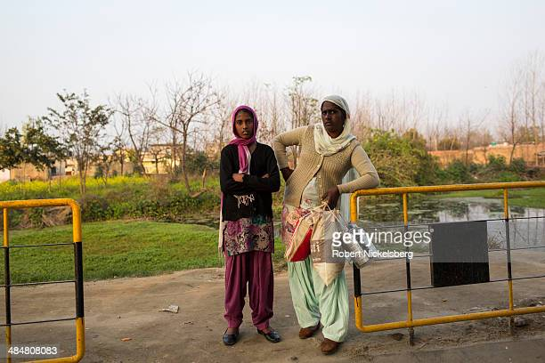 Two young women stand near a tollbooth along the Grand Trunk Road February 25 2014 west of Ropar India The Grand Trunk Road is one of Asia's oldest...