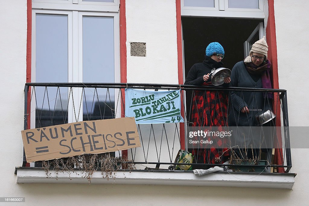 Two young women stand on a balcony next to a banner that reads: 'Eviction = Shit' at Lausitzer Strasse 8 in protest against the eviction of the German-Turkish Gulbol family from an apartment in the same house on February 14, 2013 in Berlin, Germany. Several hundred protesters arrived to demonstrate in support of Ali Gulbol, his wife and two sons, who face eviction from their apartment in Kreuzberg district despite the fact that they invested EUR 20,000 into their apartment and have paid all their outstanding rent, albeit behind schedule. The case is highlighting an ongoing controversy over gentrification in parts of Berlin, where rising housing prices are luring investors and forcing long-standing tenants out.