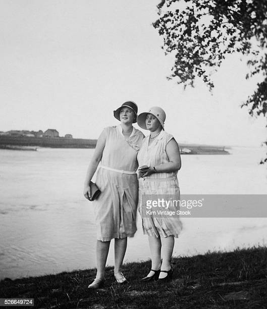 Two young women stand waterside and look off to the distance while dressed in 1920s fashions