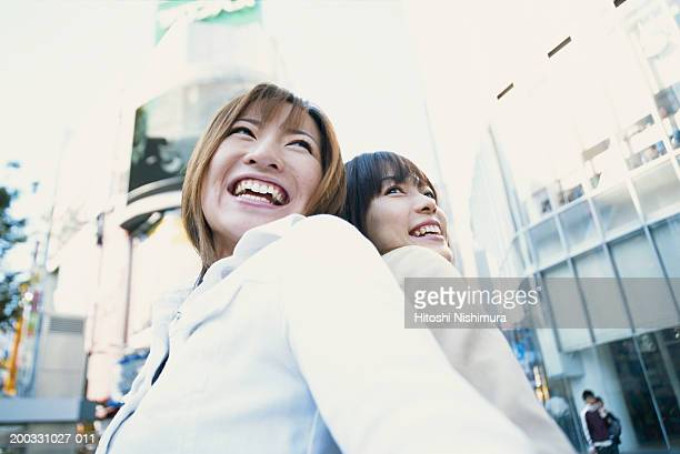 Two young women standing back to back, outdoors, low angle view