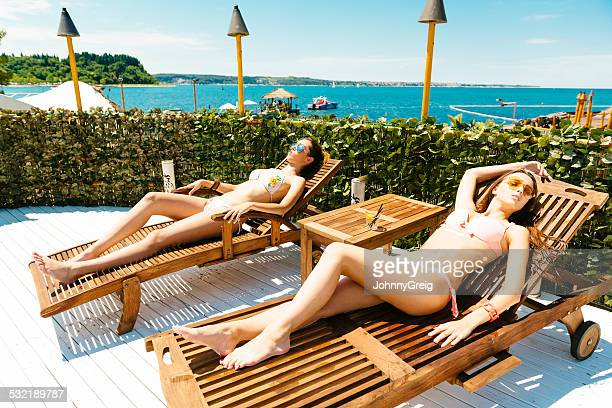 Two young women sunbathing on sunbeds