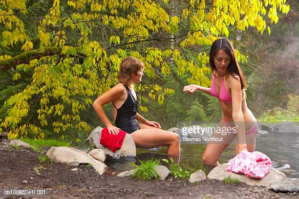 Two young women swimming in pond in forest
