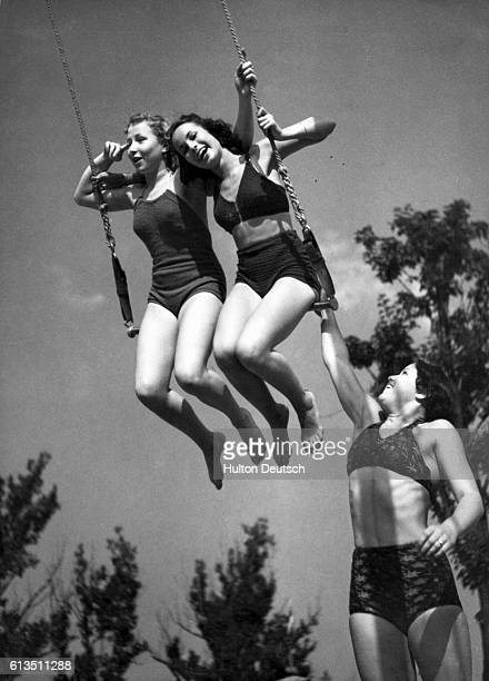 Two young women swing on a trapeze as a third young woman reaches up to give them a push