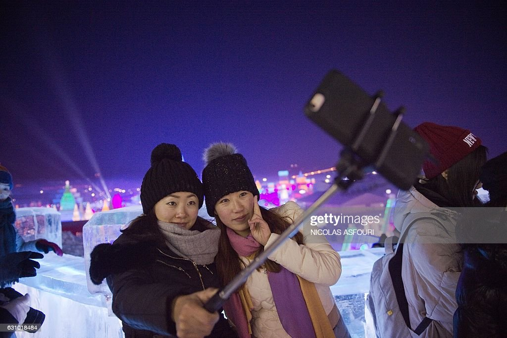 Two young women take a selfie as they visit ice sculptures illuminated by coloured lights at the Harbin Ice and Snow Festival to celebrate the new year in Harbin on January 5, 2017. / AFP / Nicolas ASFOURI