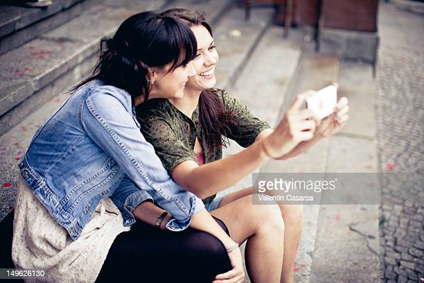 Two young women taking photograph with smart phone