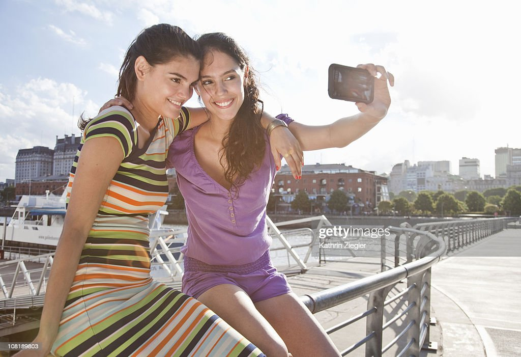 two young women taking picture with smart phone : Stock Photo