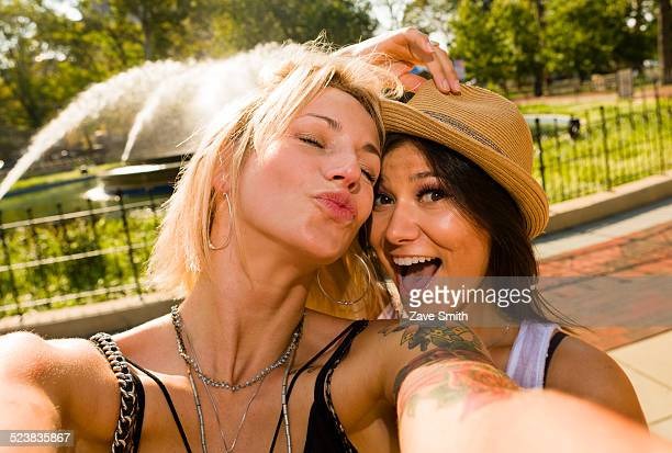 Two young women taking selfie in park