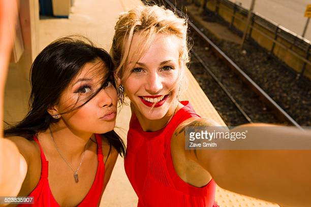 Two young women taking selfie on station platform