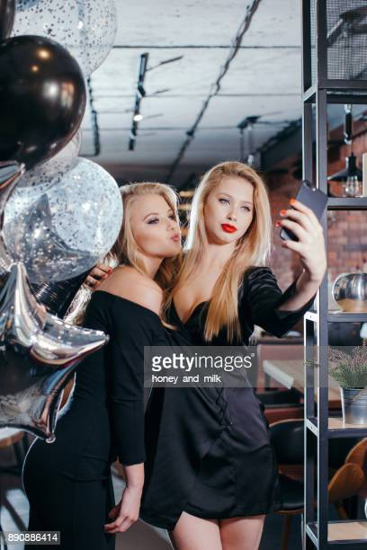 Two young women taking selfies in a cafe