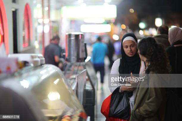 Two young women talk while waiting to be served during a street festival in the southwestern suburb of Lakemba on May 27 2017 in Sydney Australia...