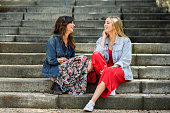 Two young women talking and laughing on urban steps. Two girls wearing casual clothes. Lifestyle concept.