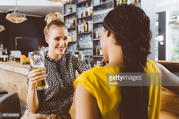 Two young women talking in a pub