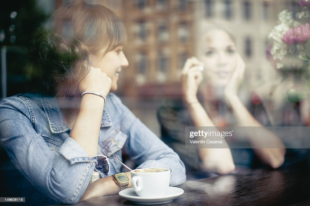 Two young women talking in cafe
