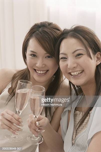 Two young women toasting champagne flute, smiling
