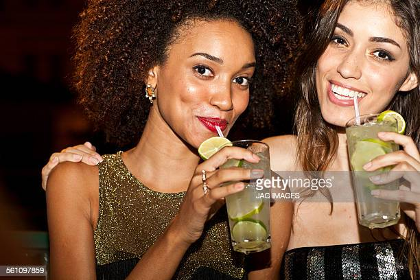 Two young women together in bar, drinking, smiling