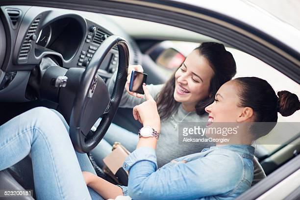 Zwei junge Frauen berühren GPS-Navigationssystem im Auto und Lächeln