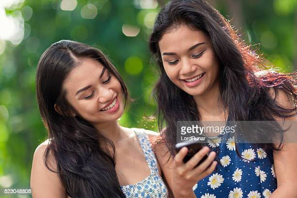 Two young women using a smartphone