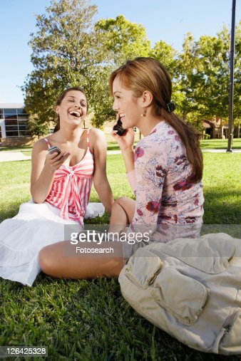 Two young women using cell phones in park