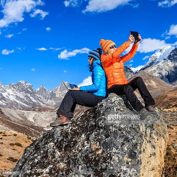 Zwei junge Frauen, die mit laptop und tablet im Himalaya, Nepal