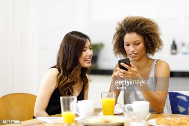 朝食をとりながら携帯電話を使用して 2 人の若い女性