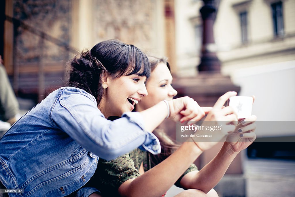 Two young women using smart phone : Stock Photo