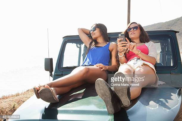 Two young women using smartphone whilst sitting on hood of jeep at coast, Malibu, California, USA