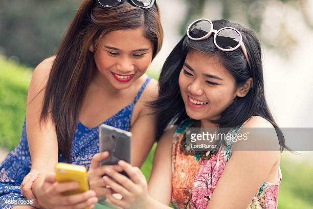 Two young women using their phones together