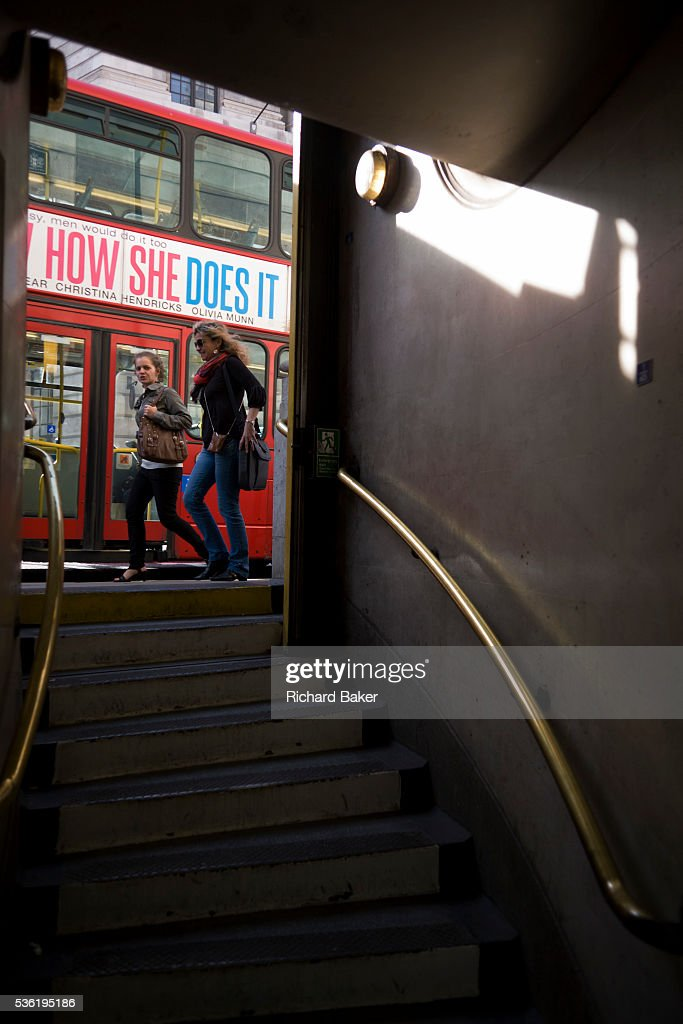Two young women walk past the entrance of London's Bank underground station whose steps go downwards from street level As they pass the exit a bus...