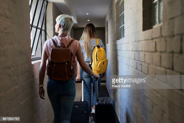 Two young women walking down isle, to check in to rental apartment