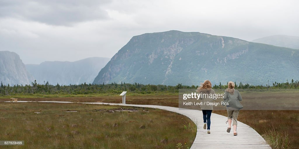 Two young women walking on a wooden boardwalk at Norris Point