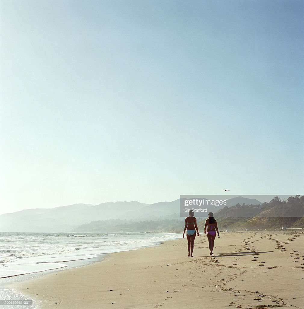 Two young women walking on beach, rear view : Stock Photo