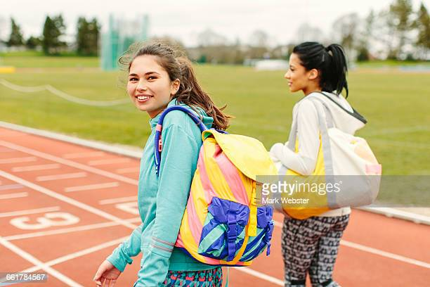 Two young women walking on running track, carrying sports bags, rear view