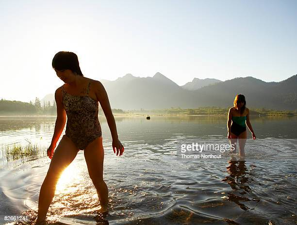 Due giovani donne che cammina lungo il lago all'alba