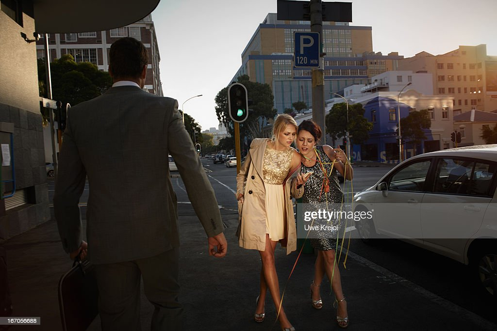 Two young women walking with smart phone in hand : Stock Photo