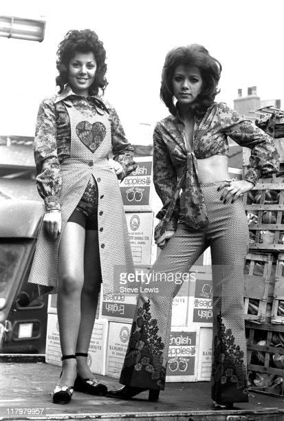 Two young women wearing 70s fashions in London's East End circa 1970