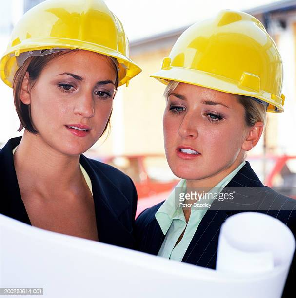 Two young women wearing hardhats, looking at blue prints