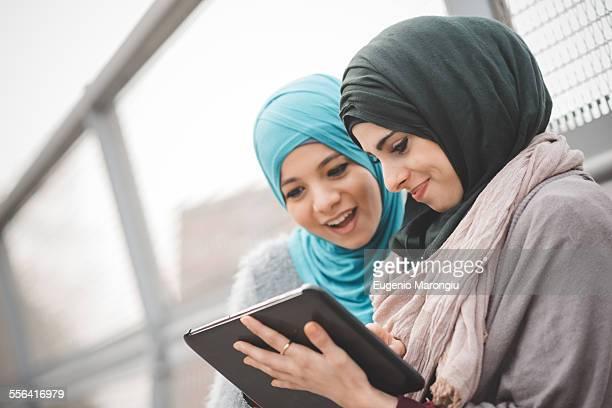 Two young women wearing hijabs using digital tablet on footbridge