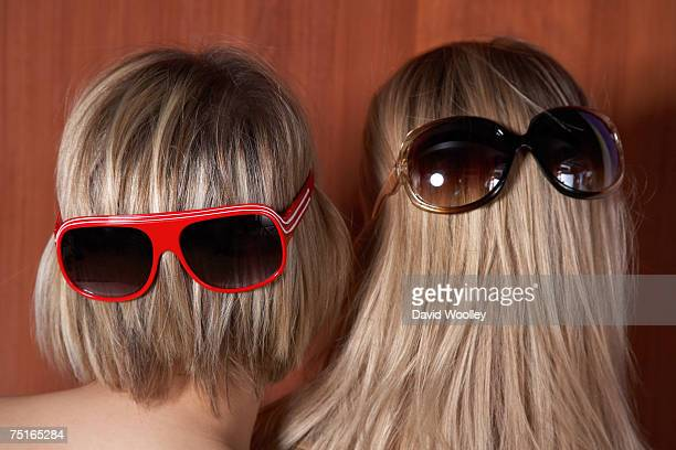 Two young women wearing sunglasses over hair, rear view, close-up